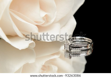 A diamond engagement ring with a white rose, shot with a reflection on a black background. - stock photo