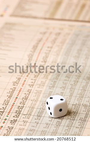 A dice sitting on a stock market chart - stock photo