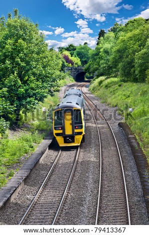 a diesel engined passenger train heading for a bridge in wales, uk. - stock photo
