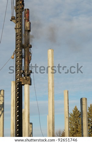 A diesel pile driver driving piles at a construction site. - stock photo