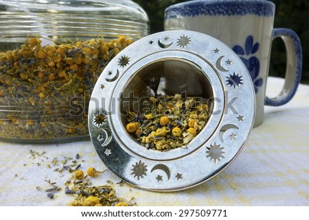 A diffuser holds a blend of loose herbal tea with lavender, chamomile and lemon verbena. - stock photo