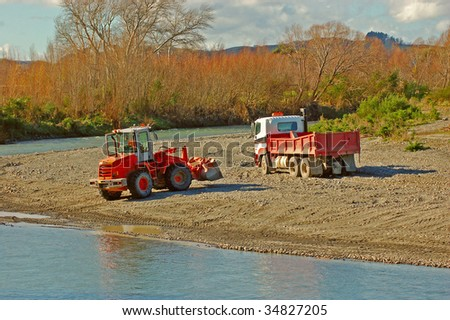 A digger and a truck collecting gravel for roading from river shore - stock photo