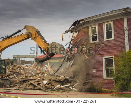 A digger demolishing a house for reconstruction. - stock photo