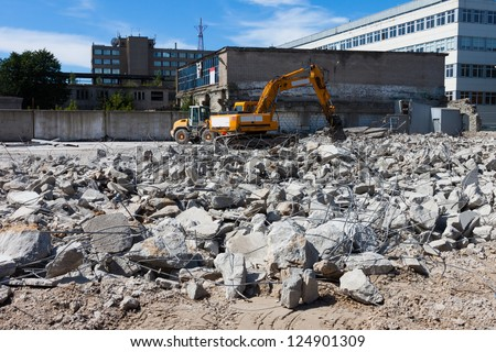 A digger demolishing houses for reconstruction - stock photo