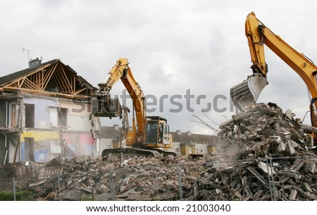 A digger demolishing houses for reconstruction. - stock photo