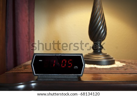 A digital alarm clock displaying 1 pm on the backlit LCD. - stock photo