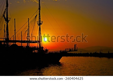 A digitally converted painting of a ship in silhouette at sunset - stock photo