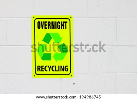 A digitally manipulated illustration of a photo of a yellow overnight recycling sign mounted on a painted cinder block wall with room for your text