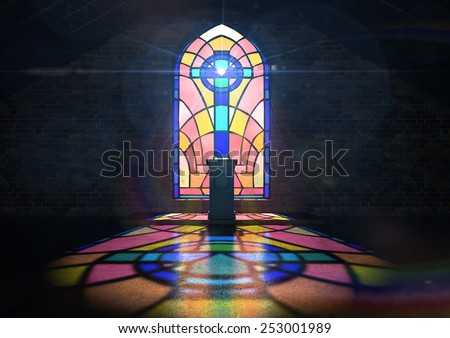 A dim old church interior lit by suns rays penetrating through a colorful stained glass window in the pattern of a crucifix reflecting colors on the floor and a speech pulpit - stock photo