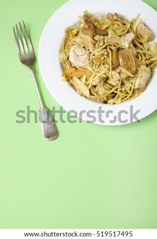 A dinner dish of chicken noodle stir fry on a pastel green background with fork and empty space below