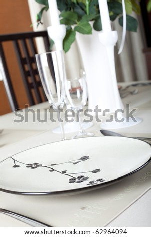 A dinner plate, knife, spoon and fork - stock photo