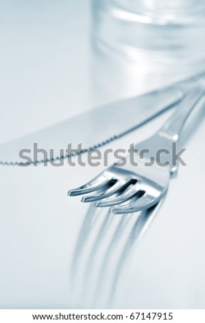 a dinner set formed by a knife, a fork and a glass