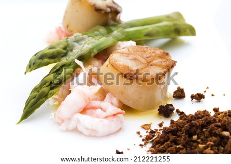 A dinnerplate with scalllops, prawns, and asparagus and onion - stock photo