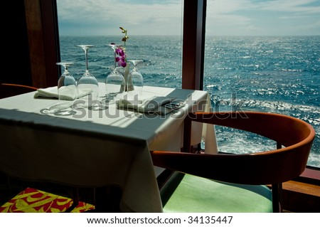 A dinning table for two on a cruise ship with blue sea water outside