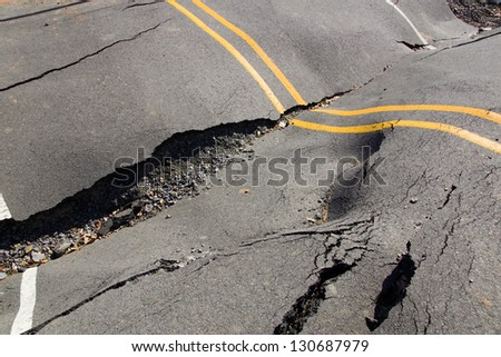 A dip in the road surface and the cracks in the asphalt - stock photo