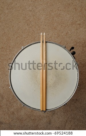 A direct overhead above view of a snare drum on a stand with drum sticks - stock photo