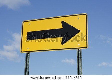 A directional arrow street sign pointing to the right. - stock photo
