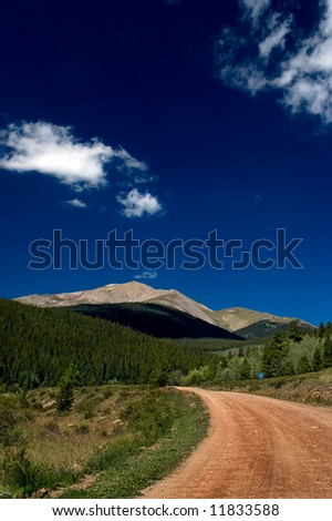A dirt road in Rural Colorado leads to the Rocky Mountains along the Continental Divide - stock photo