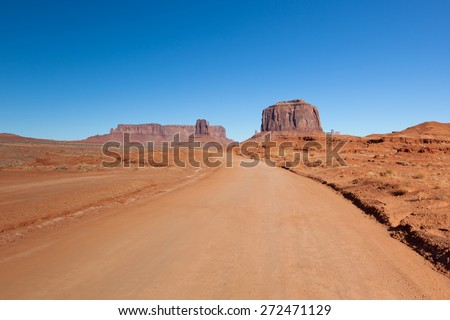A dirt road leads into the natural formations of Monument Valley in the American Southwest. - stock photo