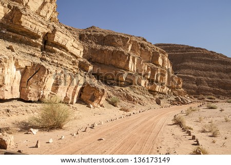 A dirt road, marked with stones; follows a line of rocky cliffs through the Negev Desert in the southern portion of Israel - stock photo