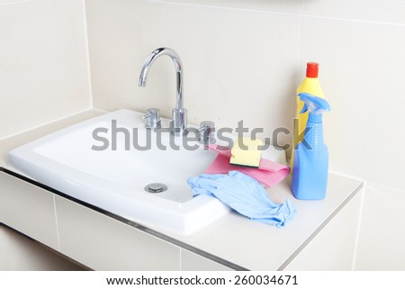 a dirty and calcified sink with cleaning gloves and cleaning products - stock photo
