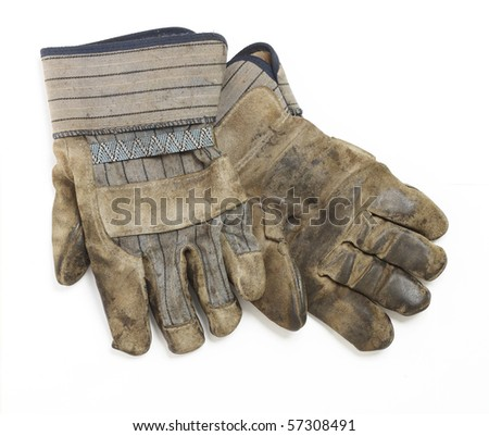 A dirty and well-worn pair of canvas and leather work gloves on white background. - stock photo