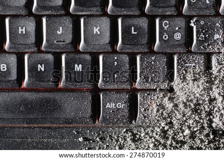 a dirty black keyboard covered in ash or dust - stock photo