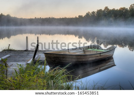 A dirty boat is parked by a wooden pier on a calm lake. It is dawn and soon the sun will be rising. - stock photo
