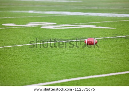 A dirty football on a professional artificial turf football field near the 30 yard line. - stock photo