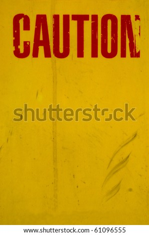 A Dirty, Grungy Yellow Caution Sign With Red Text and Copy Space - stock photo