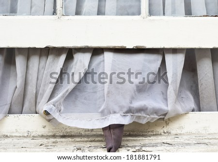 A dirty net curtain hanging out of an open window - stock photo