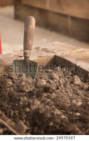 A dirty old trowel standing in the corner of an earth bed - stock photo