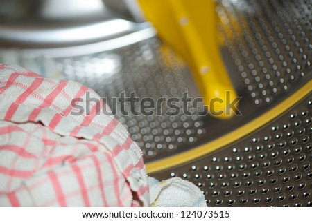A dirty towel inside a washing machine with the drum defocused - stock photo