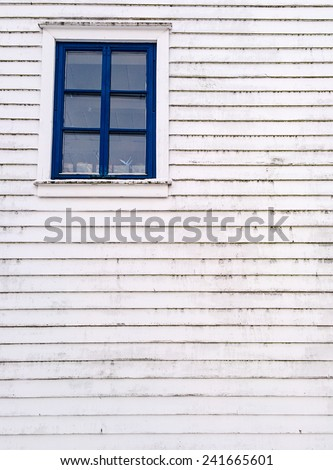 A dirty white wooden wall with a small blue-framed window - stock photo