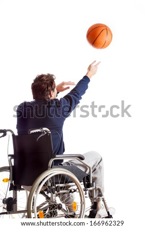 A disabled man on a wheelchair throwing a basketball - stock photo