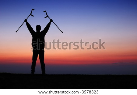 A disabled man stands on a ridge, greeting the dawn. - stock photo