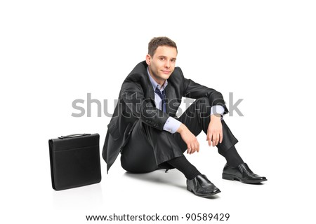 A disappointed businessman and his briefcase isolated on white background - stock photo