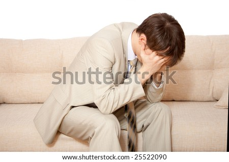 A disappointed businessman holds hands  on his face  sitting on sofa - stock photo