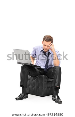 A disappointed businessman working on his and his laptop isolated on white background - stock photo