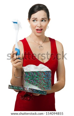 A disappointed woman looks at dish brush gift. Isolated on white. - stock photo