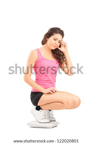 A disappointed young female standing on a weight scale isolated on white background - stock photo