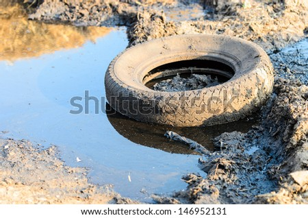 A discarded old tyre in a puddle of contaminated water - stock photo