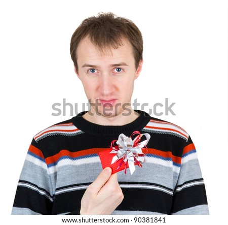A disgruntled man holding a small gift isolated on white background - stock photo