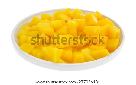 A dish filled with canned mango in small chunks isolated on a white background. - stock photo