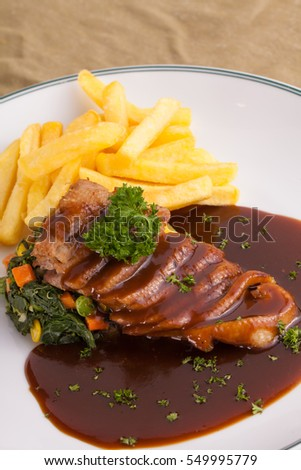 A dish of Duck breast with orange sauce served with spinach and french fries.