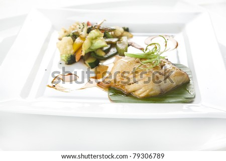a dish of fillet of fish with steamed vegetables - stock photo
