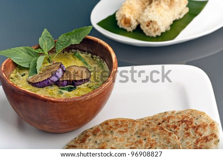A dish of fresh Thai green curry soup with pancakes and appetizers.