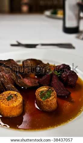 A dish of kangaroo meat with roasted beetroot and sweet potato in a gravy sauce. - stock photo