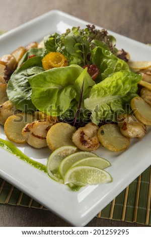 A dish of king scallop with potatoes and salad in a plate over a wooden surface