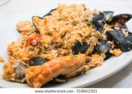 A dish of  seafood rice pics, with mussels, clams, shrimp, mussels, ready to eat, in a table spread.